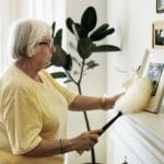 Senior woman dusting a family photo