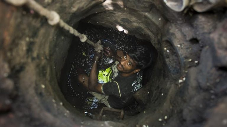 Man in india cleaning sewer drains
