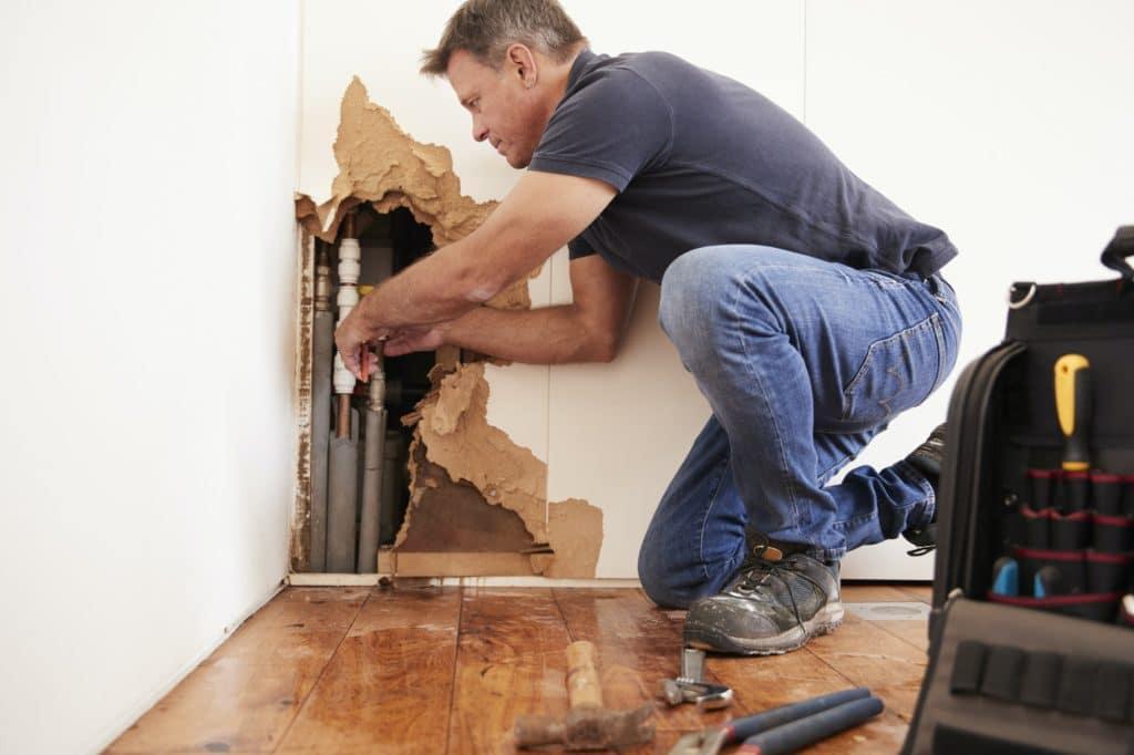 Plumber repairing burst water pipe